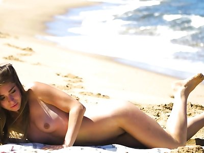 Petite body MILF Lily Chey suntanning on the beach